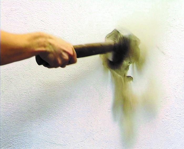 Hand holding a hammer bashing a wall